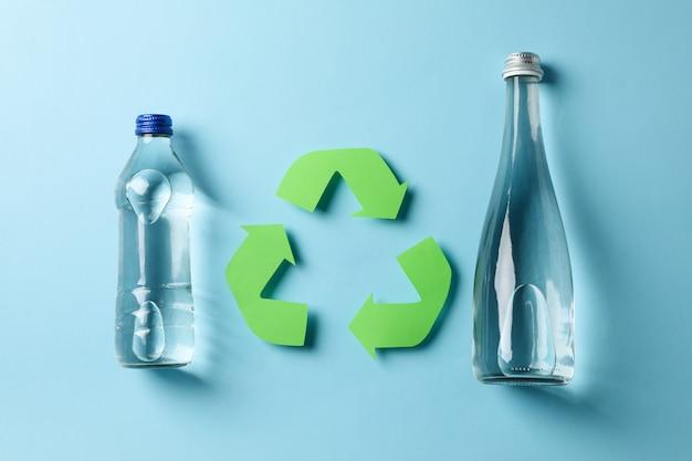 Öko-konzept mit recycling-symbol und flaschen auf blau