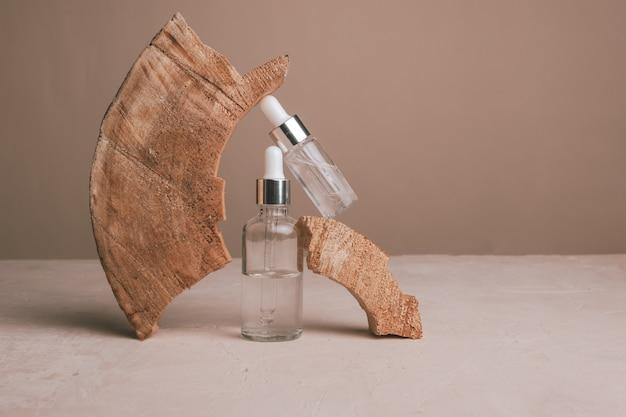 Öko-mineralöl in glasflaschen mit pipette und naturholz auf braunem hintergrund