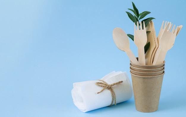 Öko-naturholzbesteck (messer, löffel, gabeln) in handwerklichem pappbecher neben papierservietten auf blauem hintergrund