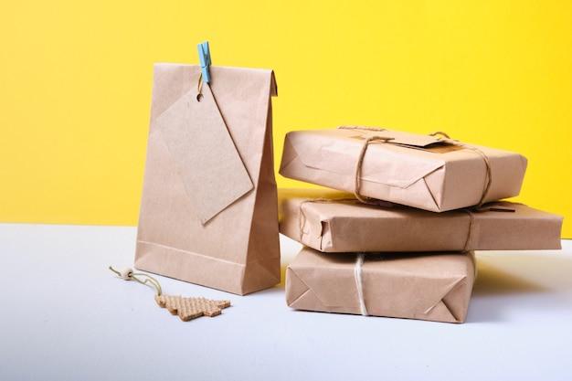 Öko-papiertüten verziert mit bändern und getrockneten tannenzweigbändern und tannenzapfen