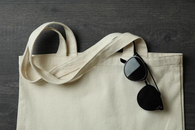 Öko-tasche mit sonnenbrille auf dunklem strukturiertem hintergrund