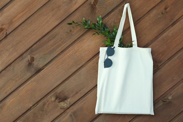 Öko-tasche mit zweig und sonnenbrille an holzwand