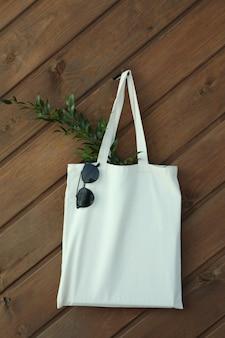 Öko-tasche mit zweig und sonnenbrille auf hölzernem hintergrund