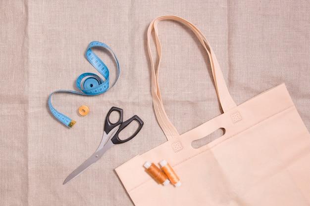 Öko-tasche, schere, maßband und mehrere garnrollen auf leinenstoff