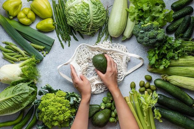 Öko-tasche und grünes gemüse. gesunder lebensmittelhintergrund. flach liegen. nachhaltiger lebensstil.