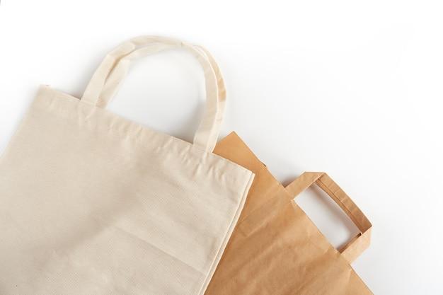 Öko-taschen aus papier und stoff auf weißem hintergrund. umweltschutzkonzept, ökologie