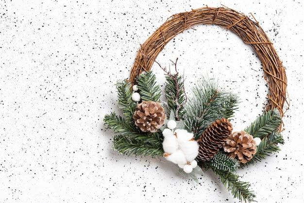 Öko-weihnachtskranz auf weißem zement. draufsicht.