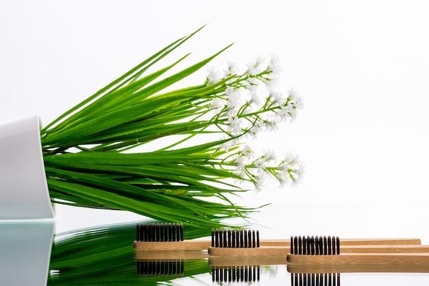 Öko-zahnbürsten aus holz auf einem tisch mit grünem ast
