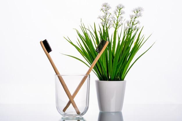 Öko-zahnbürsten aus holz in einem glasglas auf einem tisch mit grünem ast