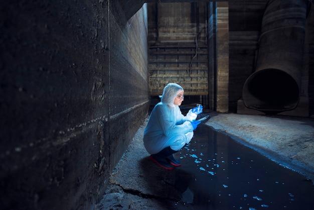 Ökologe, der wasserproben aus dem abwassersystem entnimmt und qualität und grad der kontamination und verschmutzung untersucht