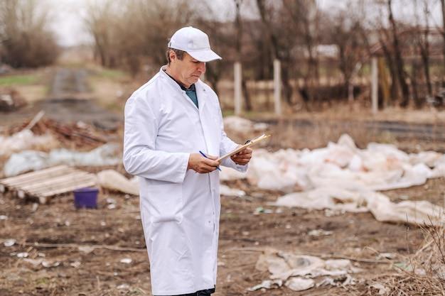 Ökologe in der weißen uniform, die zwischenablage betrachtet, während er auf deponie steht.