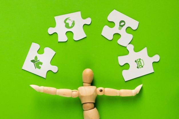 Ökologieikone auf weißen puzzlespielstücken mit dem menschlichen finger über grün