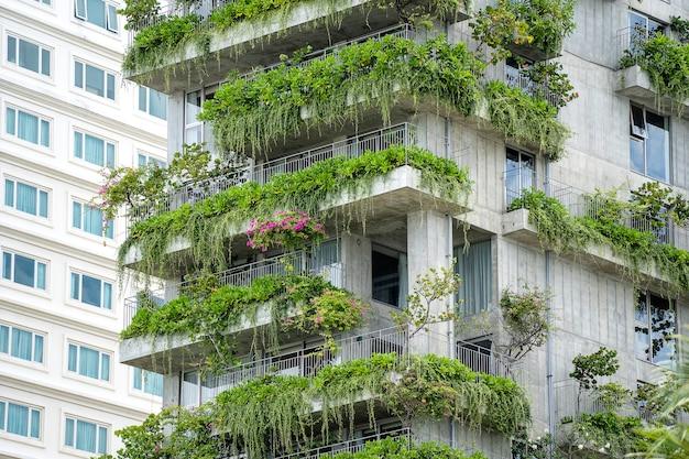 Ökologische gebäudefassade mit grünen pflanzen und blumen auf der steinmauer der fassade des hauses auf der straße der stadt danang in vietnam