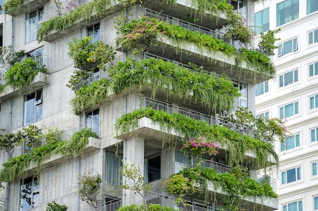Ökologische gebäudefassade mit grünen pflanzen und blumen auf steinmauer der fassade des hauses auf der straße von danang, vietnam