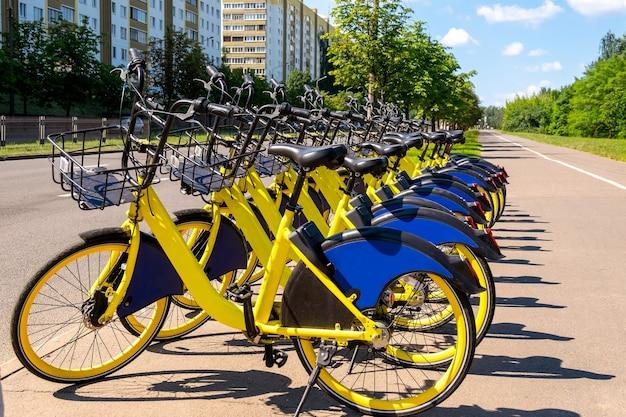 Ökologischer transport. an einer haltestelle der öffentlichen verkehrsmittel stehen viele gelbe leihfahrräder.