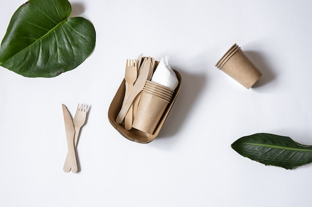 Ökologisches einweggeschirr aus bambusholz und papier. tassen, messer und gabeln isolierten draufsicht.