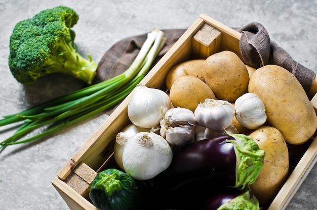 Ökoverpackung für gemüse, kunststofffrei. box mit gemüse: kartoffeln, zwiebeln, knoblauch, auberginen, zucchini, brokkoli, frühlingszwiebeln. bauernhof.