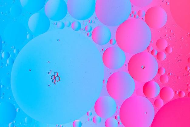 Öl auf wasser-makrofotografie des abstrakten blauen und gelben rosa gradientenhintergrunds
