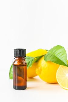 Öl in einer braunen flasche auf einem weißen mit ganzen zitronenfrüchten und blättern