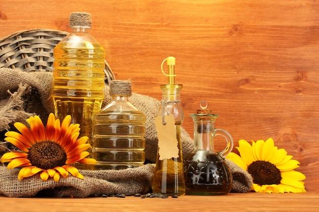 Öl in flaschen, sonnenblumen und samen, auf holz