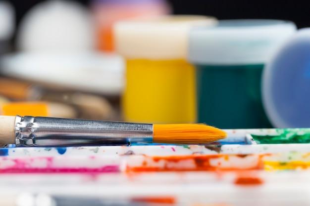 Öl und andere arten von farben während der kreativität, der kreative prozess des zeichnens einer person durch mischen verschiedener farben, gemischte mehrfarbige farben für kreativität und zeichnen