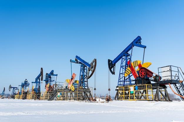 Öl-und gasindustrie. arbeitsölpumpenheber auf einem ölfeld am sonnigen wintertag. ölförderung in sibirien.