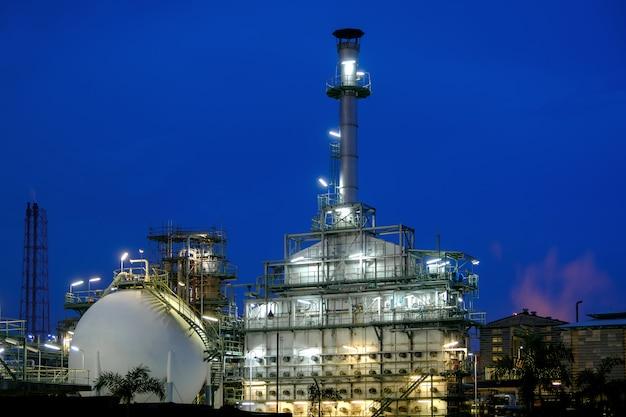Öl- und gasraffinerieanlage oder petrochemische industrieanlage auf dämmerungshintergrund des blauen himmels, erdölfabrik mit morgenhimmel, industrieofen und gerissene kohlenwasserstoffkette des schornstapels