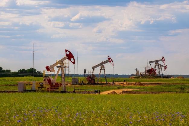 Ölbohrtürme und pumpenheber. ölbohrtürme im wüstenölfeld für die förderung fossiler brennstoffe und die rohölproduktion aus dem boden.