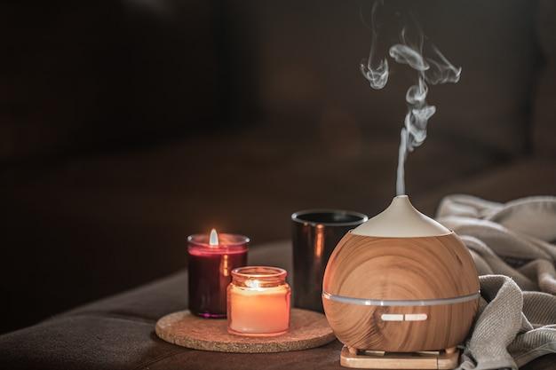 Öldiffusor auf verschwommenem raum in der nähe von brennenden kerzen. aromatherapie- und gesundheitskonzept.