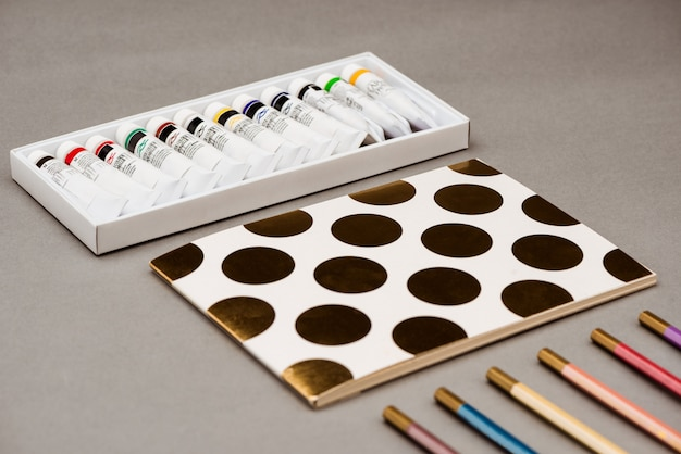 Ölfarben, bleistifte und skizzenbuch auf grauem tisch