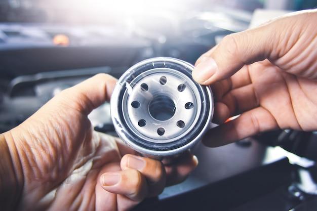 Ölfilter in der mechanikerhand für die wartung des motorölsystems in der werkstatt
