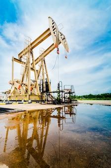 Ölpumpe bewegt sich. ölindustrieausrüstung mit blauem himmel