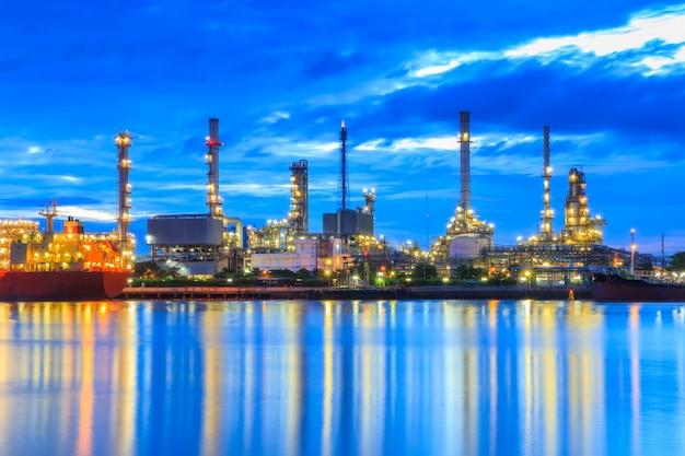 Ölraffinerie entlang des flusses in der abenddämmerung (bangkok, thailand)