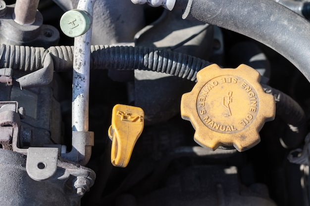 Ölsonde und öldeckel. staubige details eines motorraums mit vier flachen autos unter der offenen motorhaube.