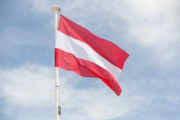 Österreichische flagge schwebt im wind, der von einem mast hängt
