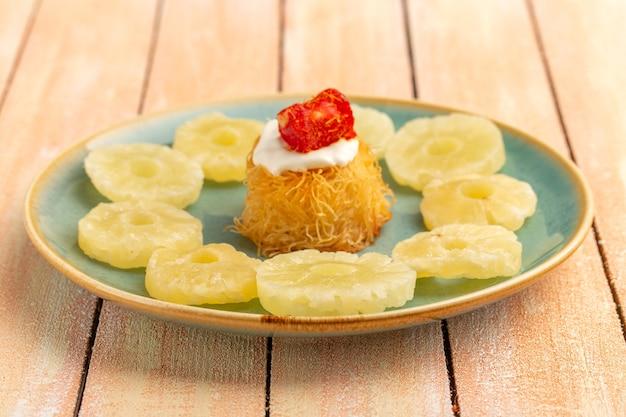 Östliche gebäckkekse innerhalb platte mit weißen cremegetrockneten ananasringen auf holztisch