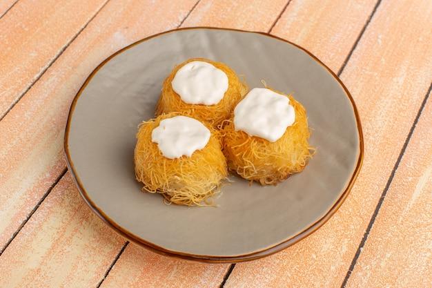 Östliche gebäckkekse innerhalb platte mit weißer creme auf holz