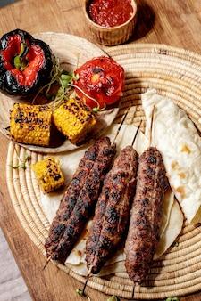Östliches fast food. gegrillter würziger rindfleisch-lyulya-kebab auf stangen auf fladenbrot mit gegrilltem gemüse zuckermais, tomate und paprika, tomatensauce auf holztisch. flach liegen