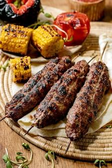 Östliches fast food. gegrillter würziger rindfleisch-lyulya-kebab auf stangen auf fladenbrot mit gegrilltem gemüse zuckermais, tomate und paprika, tomatensauce auf holztisch.