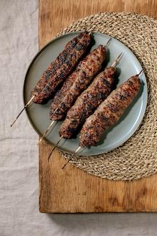 Östliches fast food. gegrillter würziger rindfleisch-lyulya-kebab auf stöcken auf keramikplatte auf holztisch mit runder strohserviette. flache lage, kopierraum
