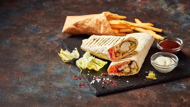 Östliches traditionelles döner, döner kebab mit hühnchen und gemüse und pommes frites mit saucen auf schiefer. fast food. östliches essen.
