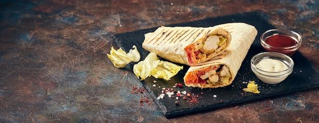 Östliches traditionelles döner mit hühnchen und gemüse, döner kebab mit saucen