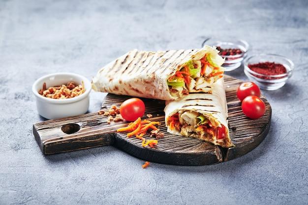 Östliches traditionelles döner mit huhn und gemüse, döner kebab mit saucen auf holzschneidebrett. fast food. östliches essen.
