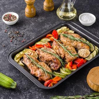 Ofen backte schweinefleisch entrecotes mit grünem pfeffer und zucchini auf backblech, auf einem dunklen hintergrund.