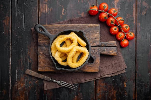 Ofen gebackene panierte calamari-ringe auf gusseiserner bratpfanne, auf altem dunklem holztischhintergrund, draufsicht flach