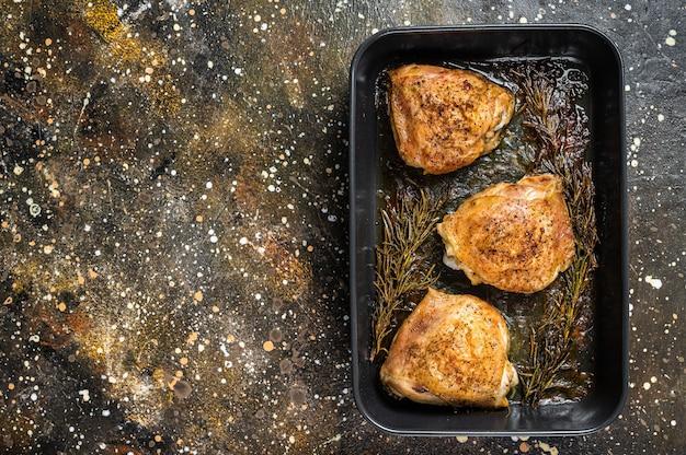 Ofen gebratene hähnchenschenkel mit gewürzen in auflaufform. brauner hintergrund. ansicht von oben. platz kopieren.