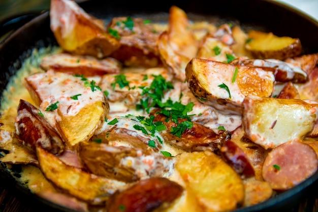 Ofenbackkartoffeln mit sahne und käse im schwarzen in einer bratpfanne auf holztisch