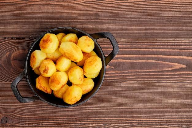 Ofenkartoffel in der roheisenbratpfanne auf natürlichem hölzernem