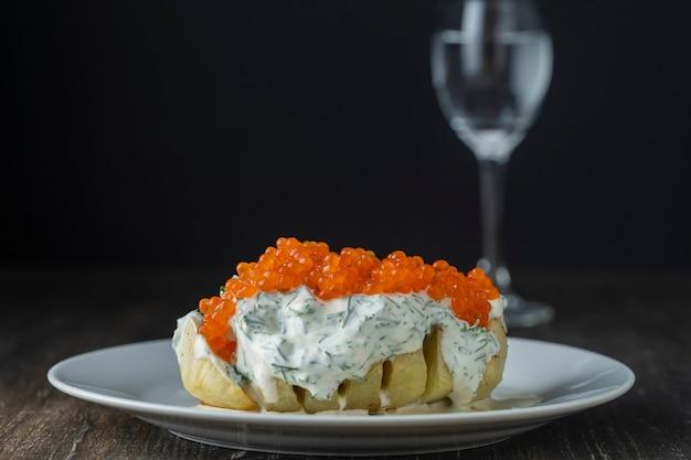 Ofenkartoffel mit cremiger käsesauce, gewürzt mit dill und rotem lachskaviar in weißer platte, nahaufnahme