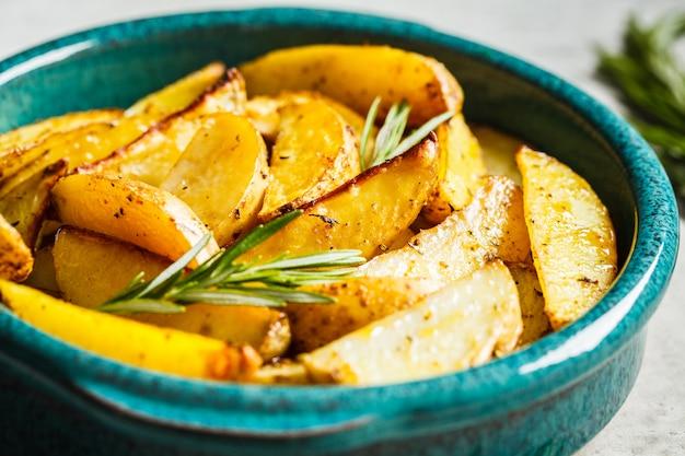 Ofenkartoffel zwängt mit rosmarin im blauen teller. gesundes veganes lebensmittelkonzept.